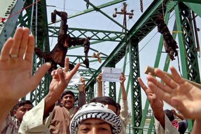 Iraqis chant anti-American slogans as charred and mutilated bodies of U.S. contractors hang from a bridge over the Euphrates River in Fallujah