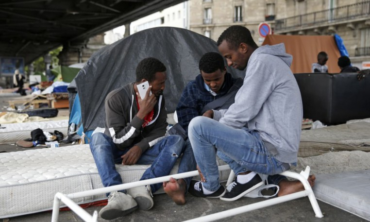 Migrants from Eritrea sit near tents as they live in a make-shift camp under a metro bridge in Paris