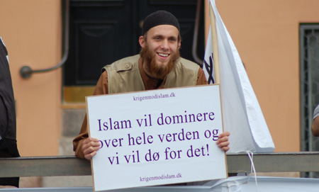 """Smiling Danish Muslim hold sign that says """"Islam will dominate the world"""""""