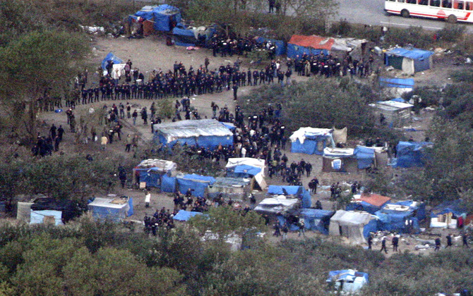 """Police officers surround  makeshift illegals camp known as the """"Jungle"""" in Calais"""