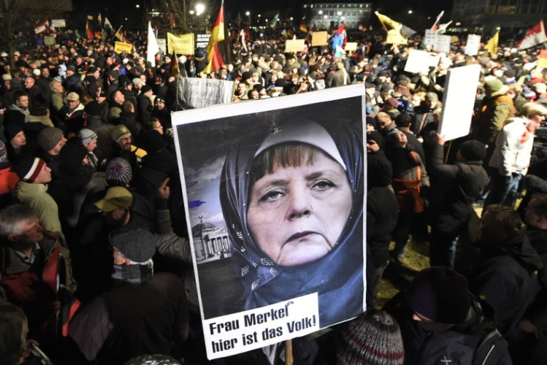Posters showing Chancellor Angela Merkel in a Muslim headbag are appearing at every anti-Muslim invader protest