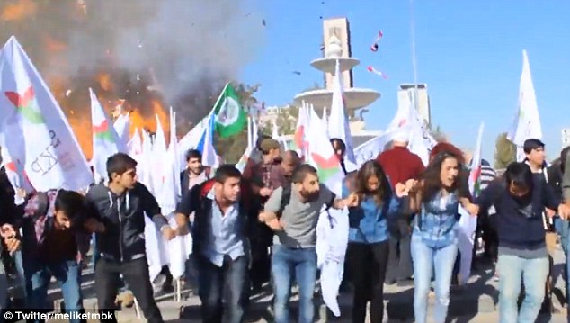 Terrifying: Peaceful demonstrators at the pro-Kurdish rally react as the powerful blast (pictured) goes off behind them