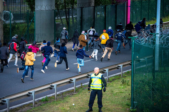 migrants-running-fence-man-jacket-reflective-green-358392