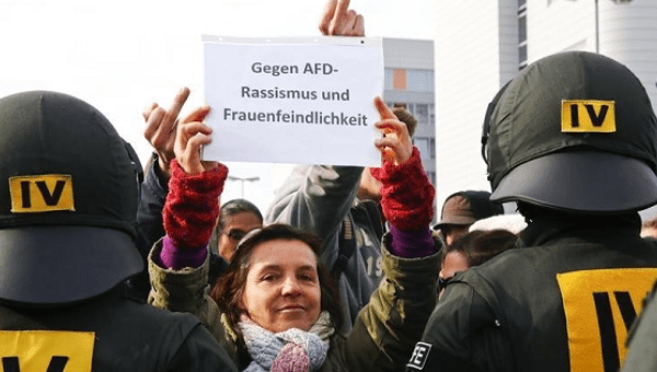 Anti-AFD leftist protesters hold a banner reading 'Against AFD racism and misogyny' during the AFD party congress in Stuttgart,