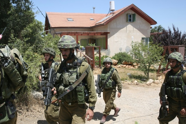 Israeli soldiers guard home of victim's family