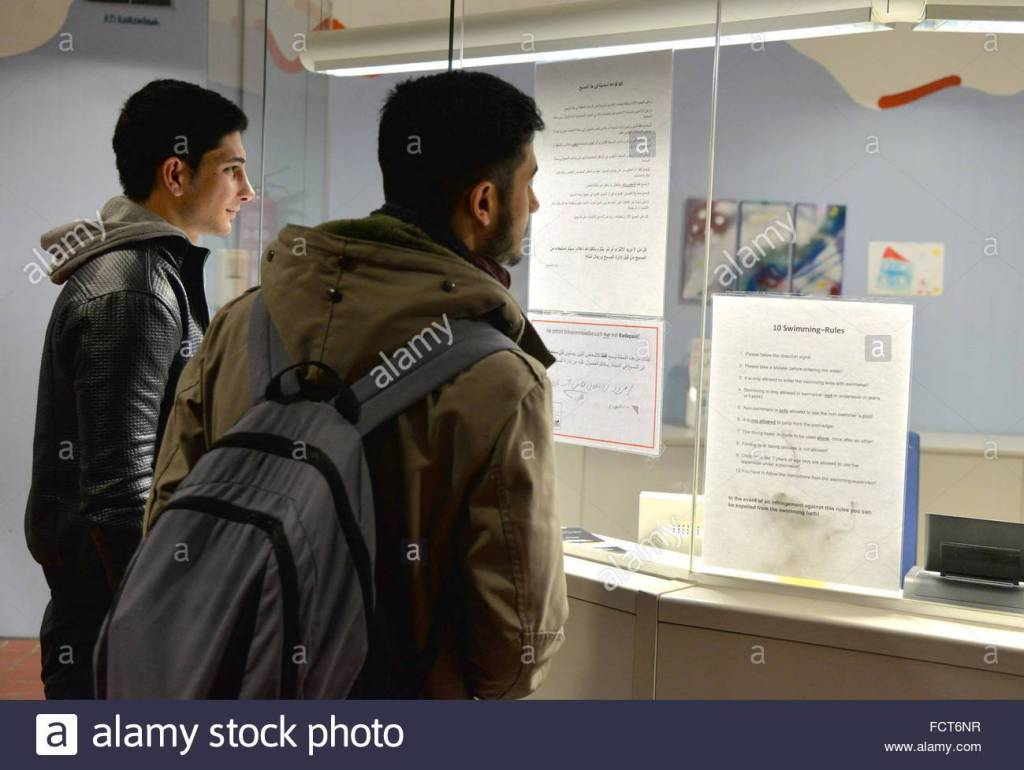MUSLIM refugees Mohsen and Ali (l) reading the pool rules written in German, Arabic and English in the swimming pool in Hermeskeil, Germany, 21 January 2016. Both own a swimming pass, which allows them to use the pool