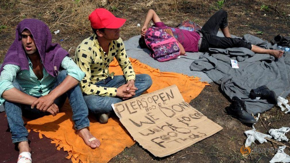 migrants-sit-on-a-field