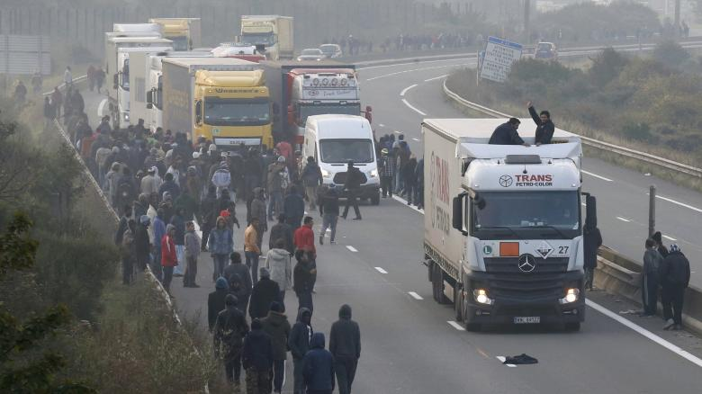 Migrants-gather-on-the-road-as-others-board-a-lorry-on-the-access