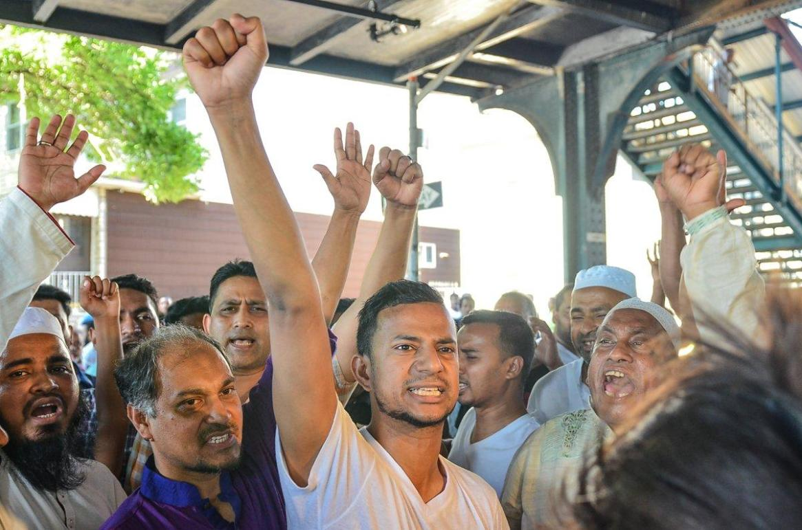 Khairul Islam Kukon, 33, surrounded by other members of the Al-Furqan, Jame Masjid, Inc. mosque, leads a chant against Donald Trump after his imam was killed in Ozone Park, Queens.