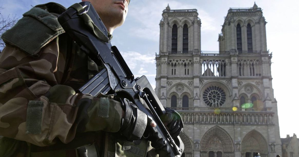 an-armed-french-soldier-patrols-in-front-of-notre-dame-cathedral