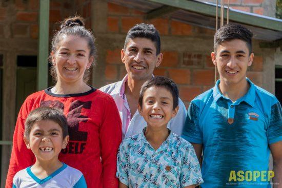 Una familia de la cooperativa ASOPEP sonríe.  Hay una madre, un padre y tres hijos.