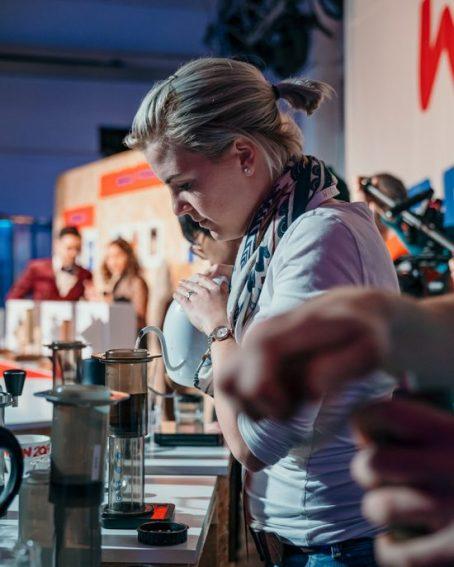 Wendelien Van Bunnik, el último campeón de AeroPress, está vertiendo agua de una tetera en el AeroPress.  Ella es rubia y lleva el pelo recogido en una coleta y tiene puesta una camiseta blanca.