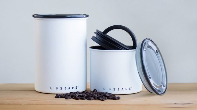 A product shot of white airscape cannisters. A handful of beans sits at the front.