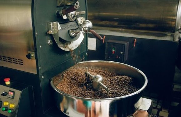 Una foto de primer plano de un tostador de café frijoles tostados.