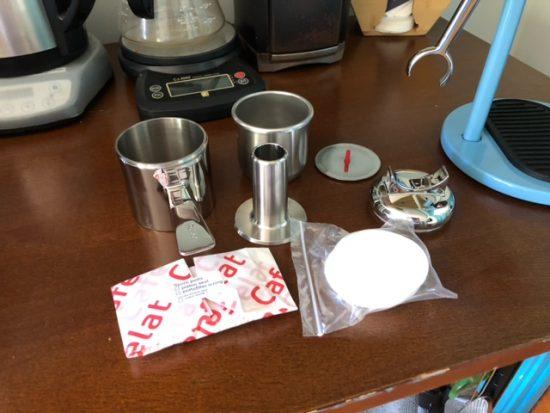 Las piezas que vienen con el cafelat, todos pequeños objetos de metal pesado envueltos en papel.