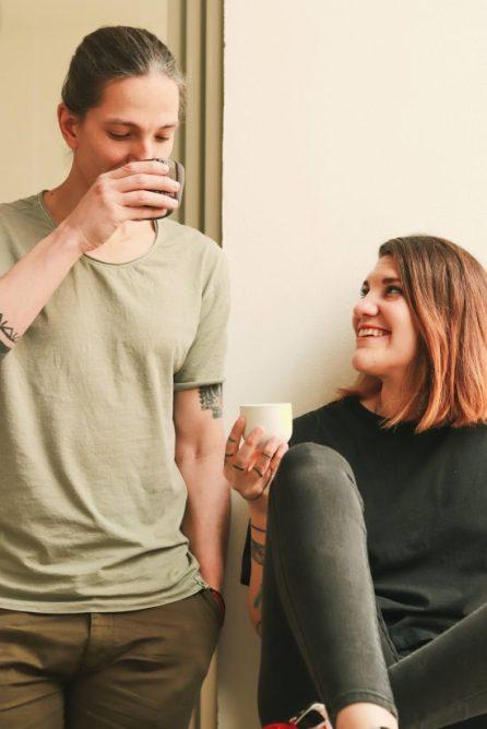 Alan mide alrededor de 6'2.  Está de pie tomando un café junto a su pareja, una mujer de cabello anaranjado teñido de longitud media que lo mira sonriendo.