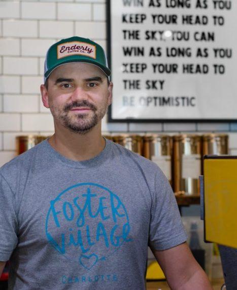 Tony es un hombre blanco con bigote y perilla.  Lleva una gorra de béisbol de primera y mira a la cámara detrás de la barra de su tienda.
