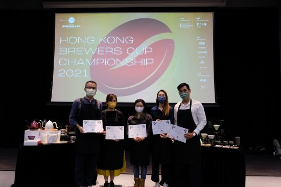 Los jueces y los ganadores se paran juntos en una fila posando para fotos frente a un proyector con los resultados.