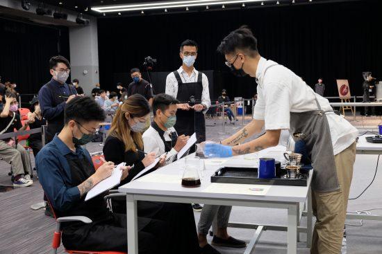 Tres jueces se sientan con máscaras faciales escribiendo en portapapeles.  Un competidor está presentando su café a los jueces.