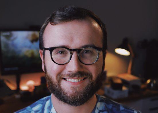 Caleb Stultz es un hombre blanco de unos 20 años.  Sonríe para un retrato.  Tiene gafas de montura gruesa, cabello moreno y una barba morena espesa.