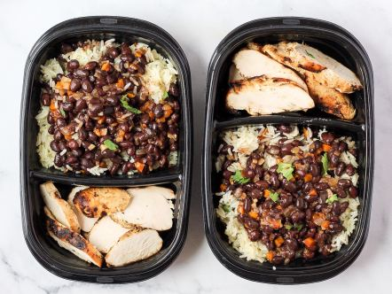 Meal prep containers with beans and rice and chicken