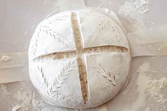 sourdough bread dough after being scored before baking