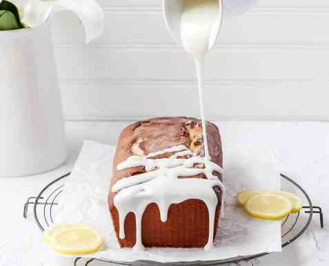 loaf cake being drizzled with lemon icing