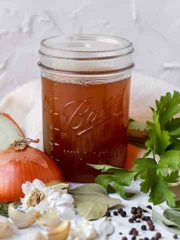 homemade vegetable stock with veggie scraps around the jar