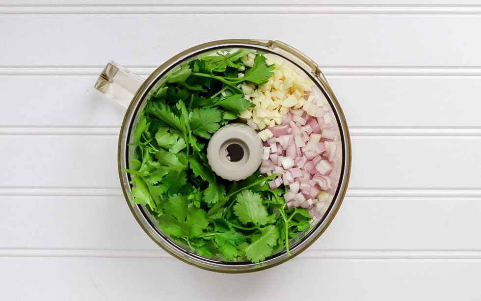 food processor bowl with ingredients for chimichurri sauce