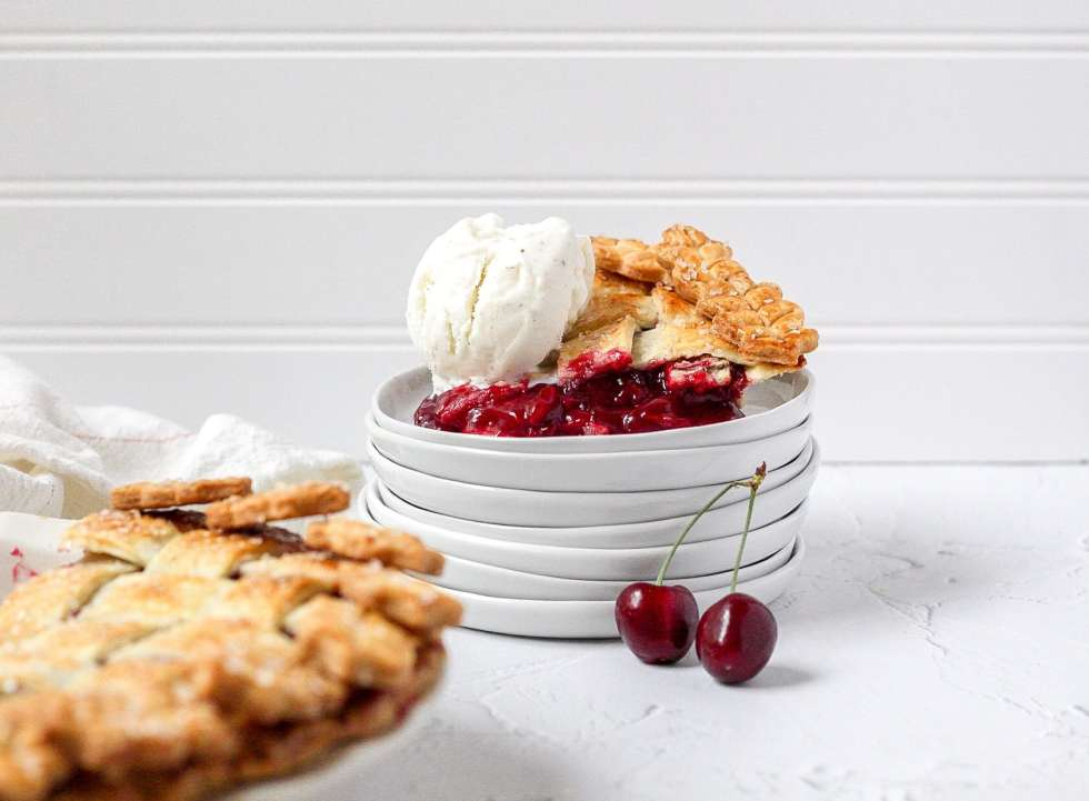 slice of cherry pie on stacked plates with ice cream on top