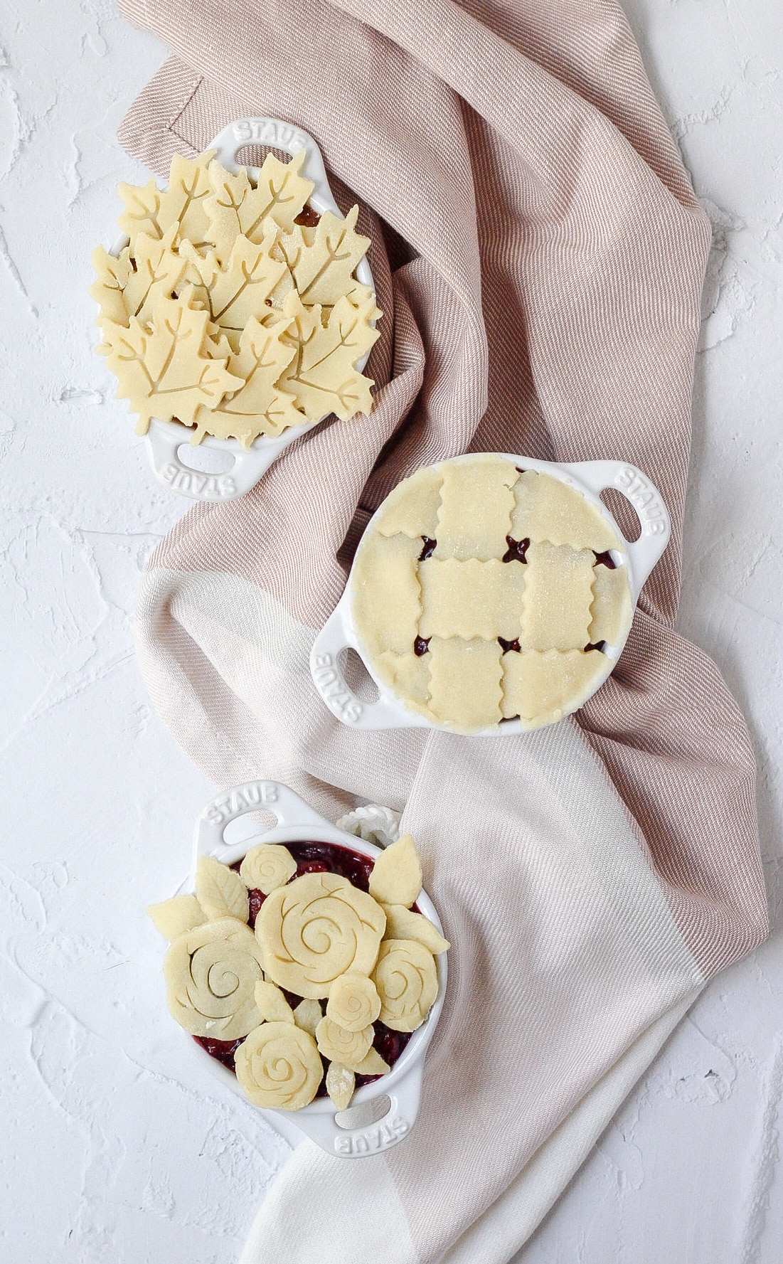 three mini pies in staub cocottes with different crust designs