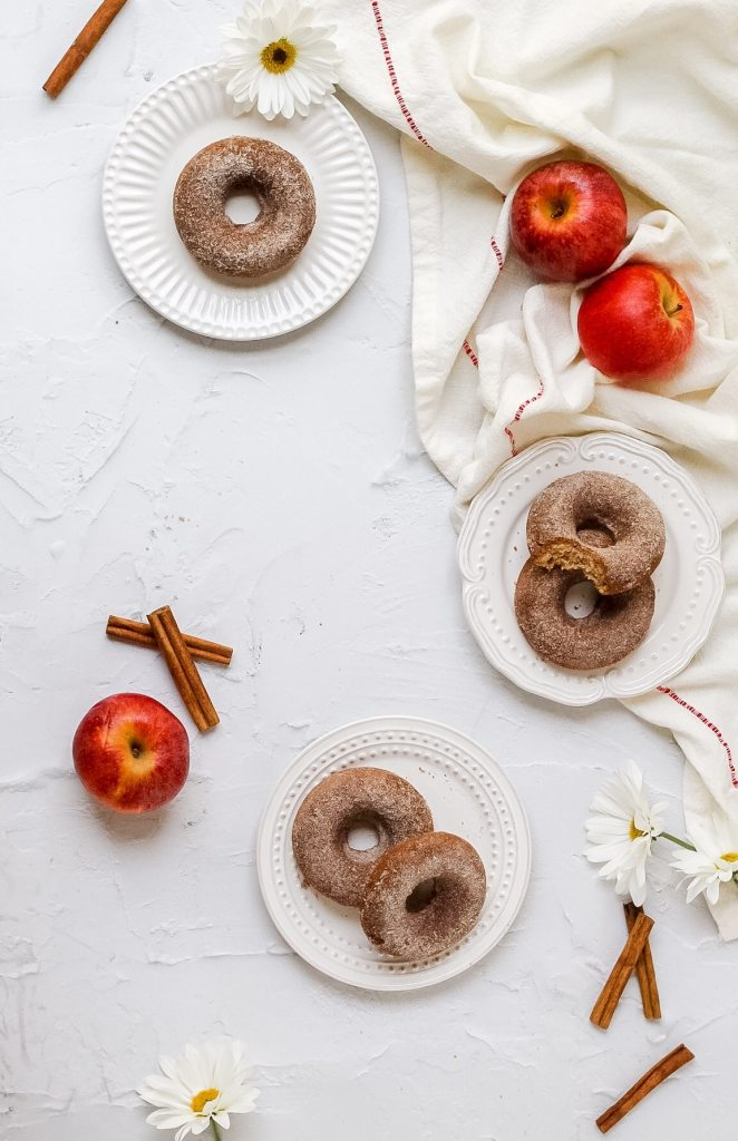 brown butter apple cider baked donuts on small plates with apples