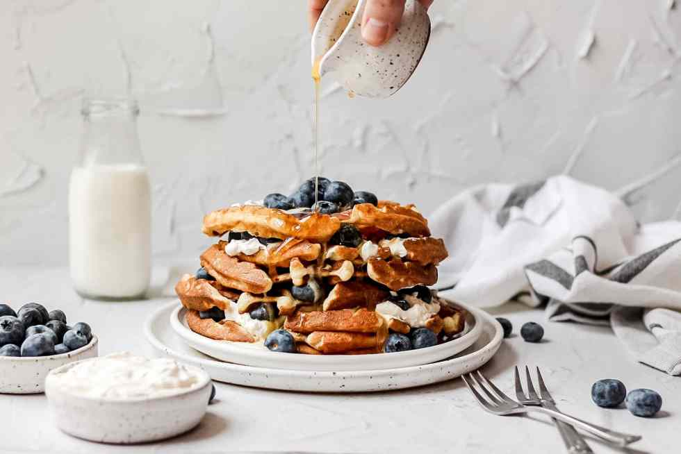 sourdough discard waffles topped with whipped cream, blueberries, and honey