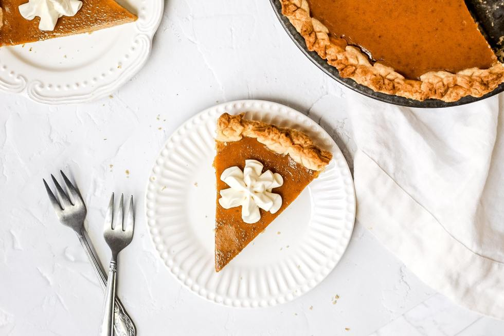 slice of bourbon pumpkin pie with whipped cream on top