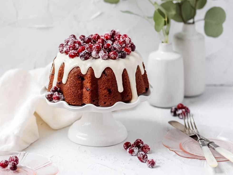 cranberry bundt cake with vanilla glaze and sugared cranberries on cake stand