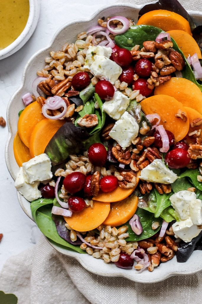 close up of persimmon salad with farro, cranberries, goat cheese, pecans, and shallots