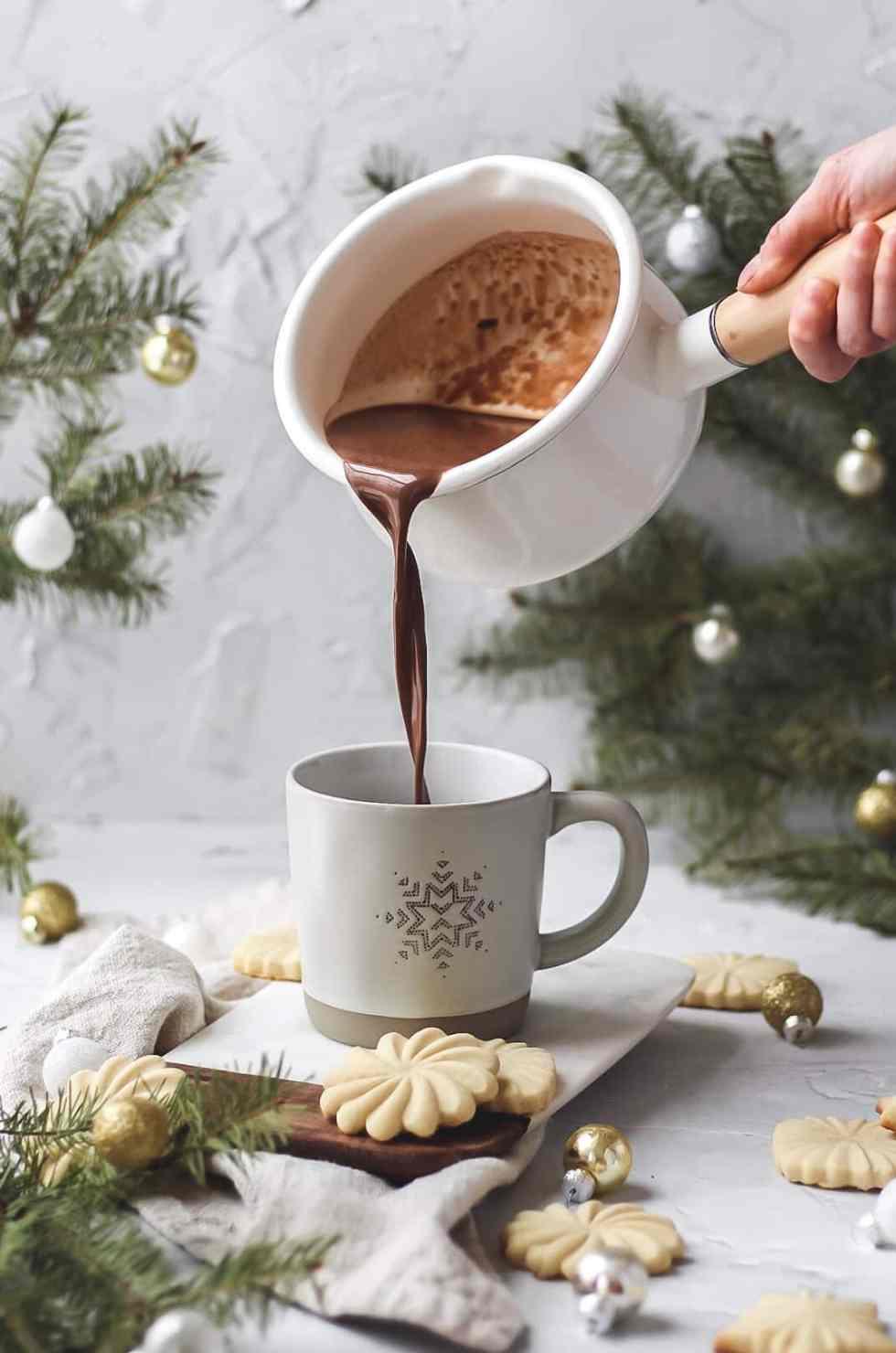 homemade cinnamon hot chocolate being poured into mug