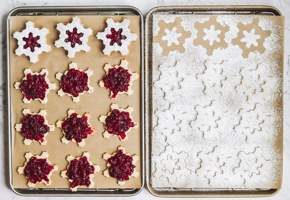 cranberry linzer cookies shaped like snowflakes  before being assembled