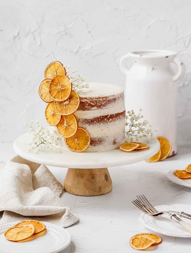 orange cardamom cake on stand with orange slices