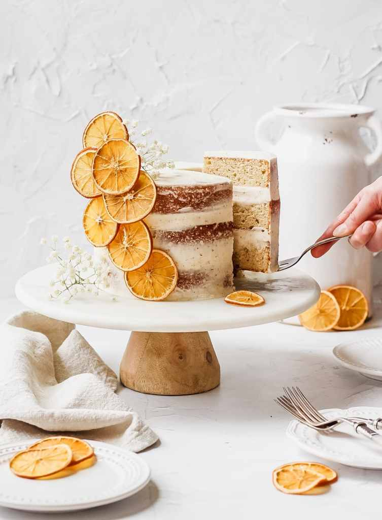 brown butter orange cardamom layer cake with layers of fluffy honey brown butter buttercream and dried orange slices