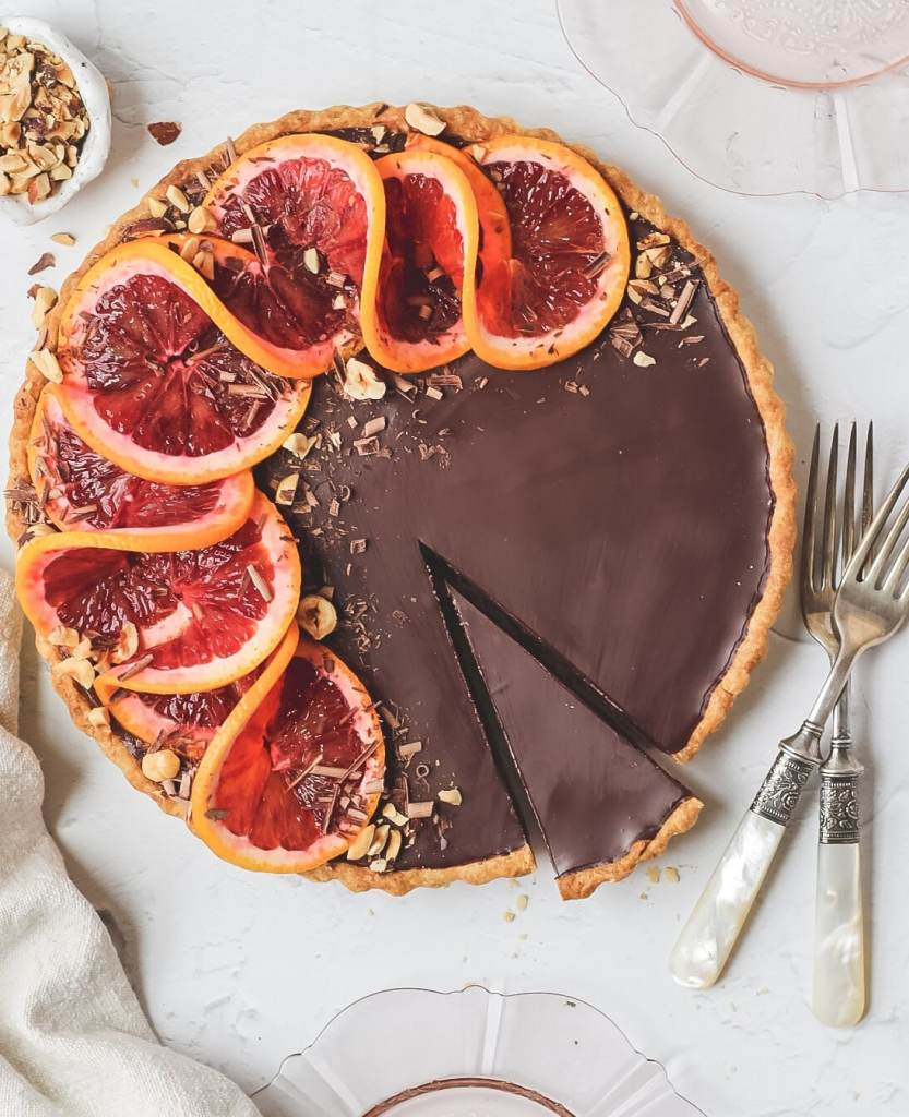 blood orange hazelnut chocolate tart topped with sliced blood oranges