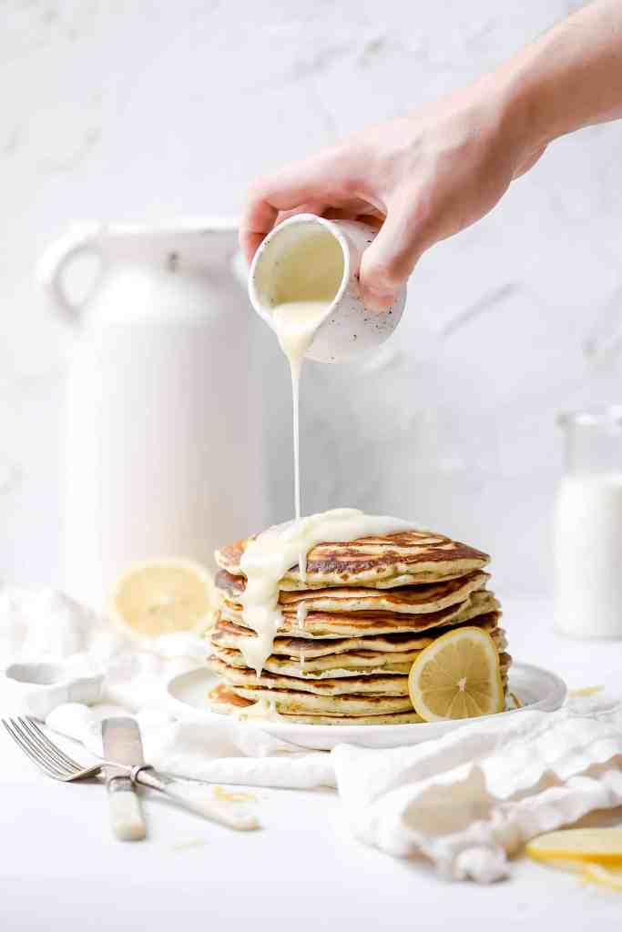 lemon poppy seed sourdough pancakes  with icing being poured on top