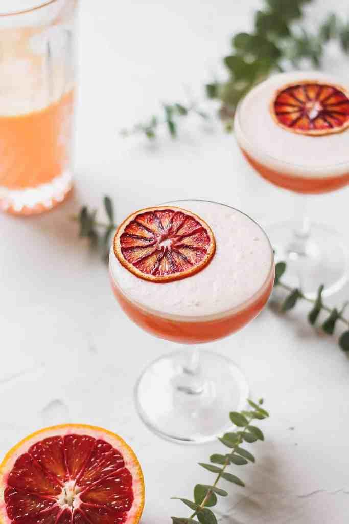 blood orange vodka sour with dehydrated orange slice on top