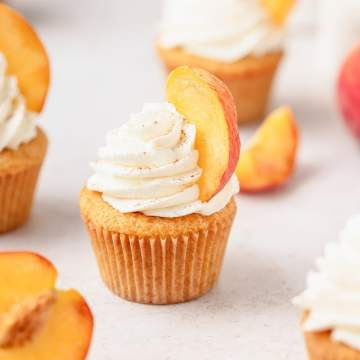 peaches and cream cupcakes with sliced peaches on top