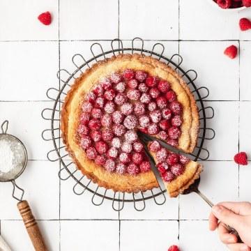 close up shot of raspberry almond frangipane tart with fresh raspberries on top