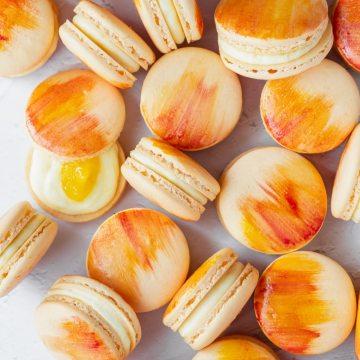up close shot of watercolor mango macarons