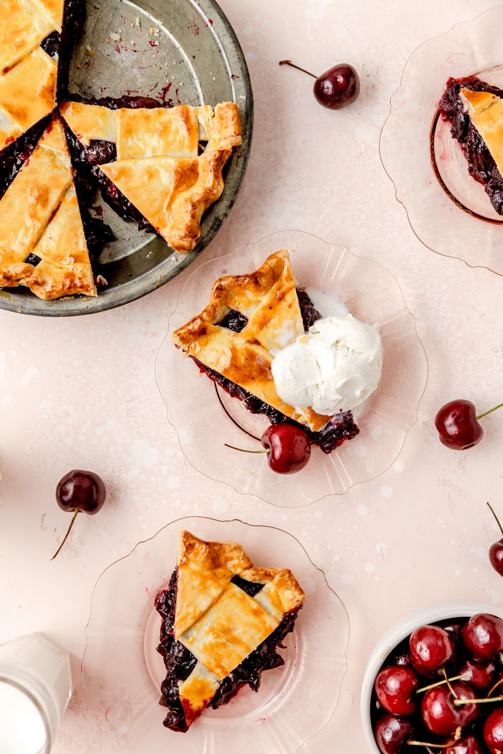 slice of cherry pie on plate topped with vanilla ice cream