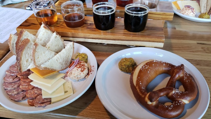 a plate with sausage slices, cheese, and bread, next to a plate with a large pretzel, with a flight of four dark beers behind them