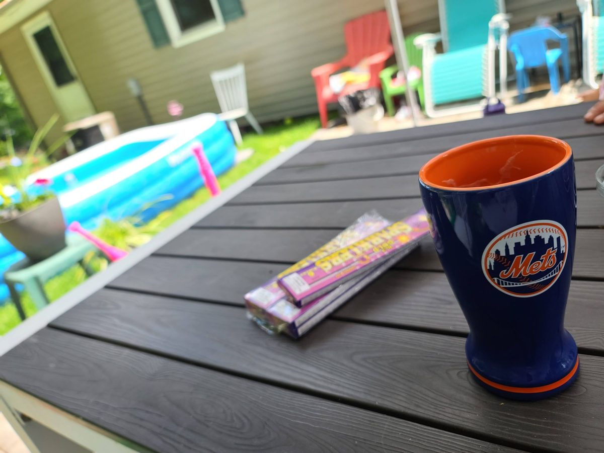 a shot of a picnic table, with a blue and orange ceramic Mets glass in the forefront, and an out of focus patio with inflatable pool and lawn chairs in the background.
