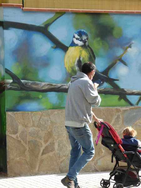Un padre con su hijo delante del pájaro en la pared